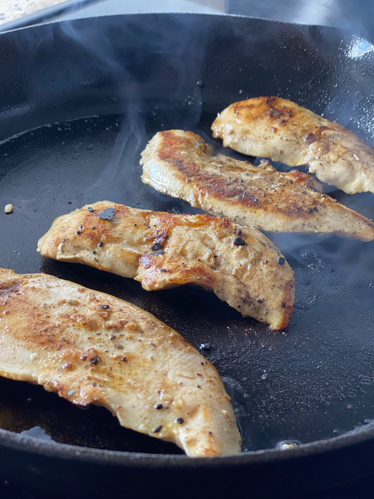 sous vide chicken breast tenders searing in a cast iron pan