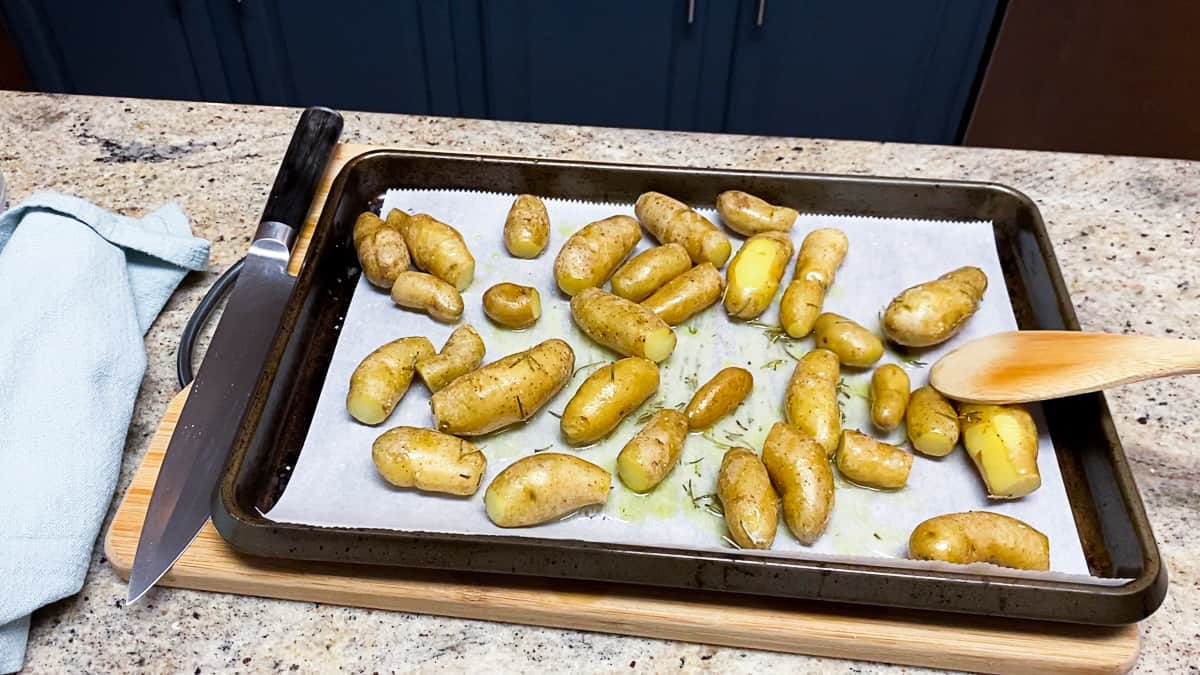 top shot of small roasted potatoes on parchment paper and baking sheet