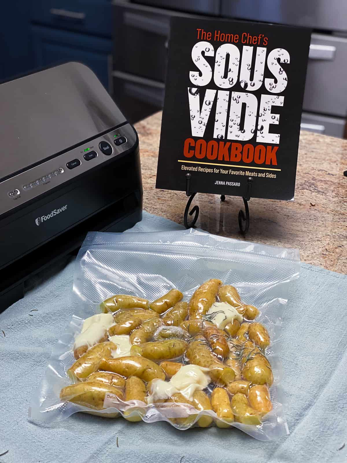 sous vide cookbook next to vacuum sealed fingerling potatoes