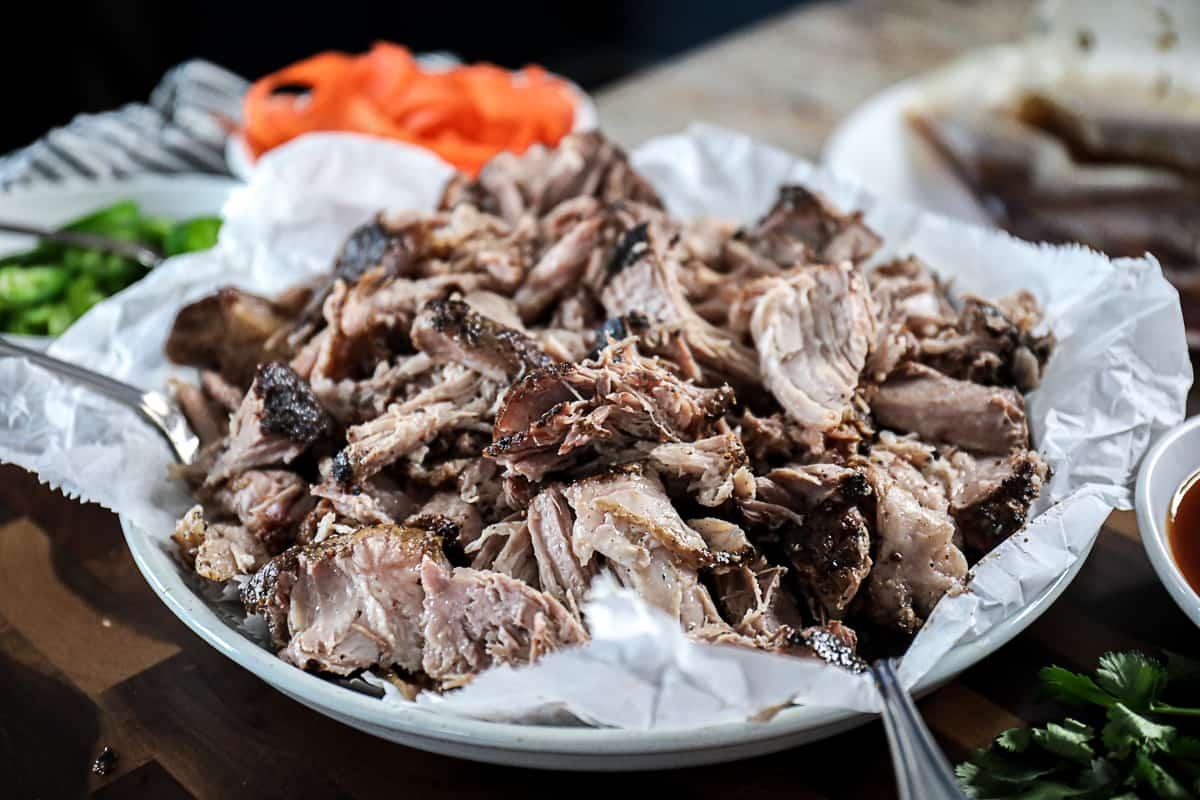 Side shot of sous vide pulled pork shoulder in a serving dish.