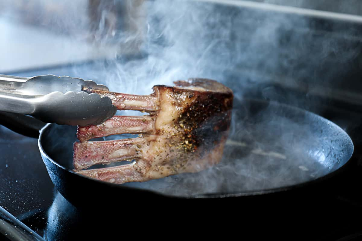 cooked rack of lamb being seared in black skillet