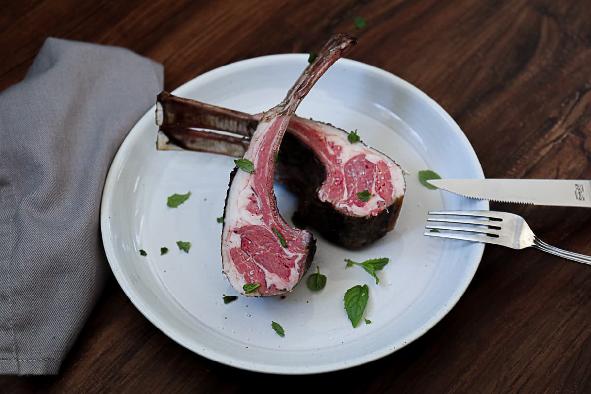 rack of lamb on white plate next to fresh mint leaves