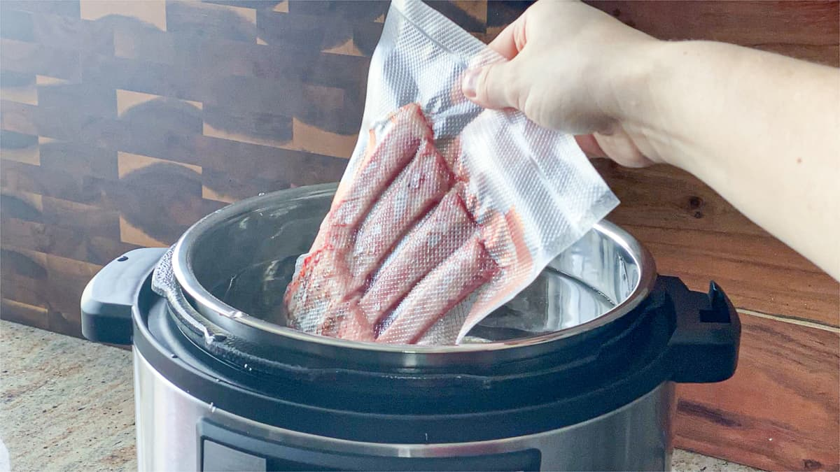 sealed bag of meat being placed in water bath