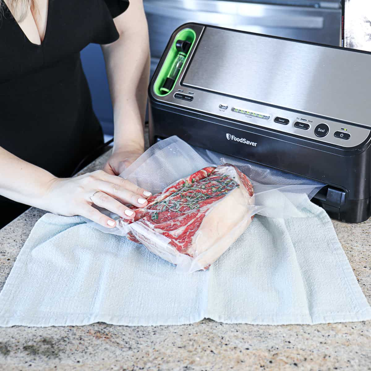 Raw steak with thyme in plastic bag being vacuum sealed