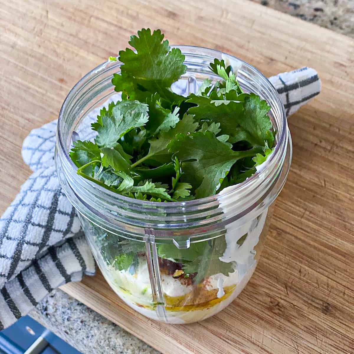 top shot of garlic cilantro sauce ingredients in blending cup