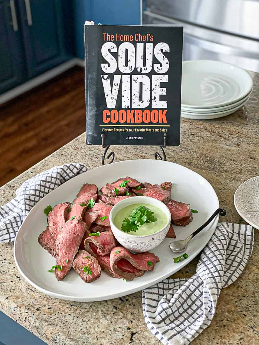 sous vide cookbook on book stand next to white plate of sliced meat with green sauce