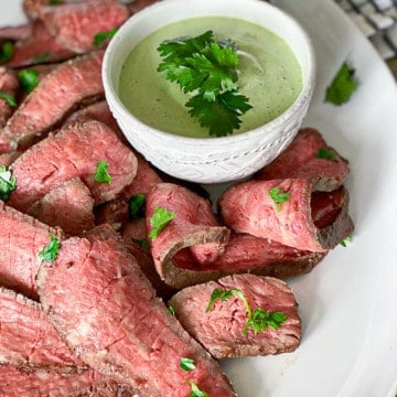 sliced steak on white plate next to small white bowl of green sauce