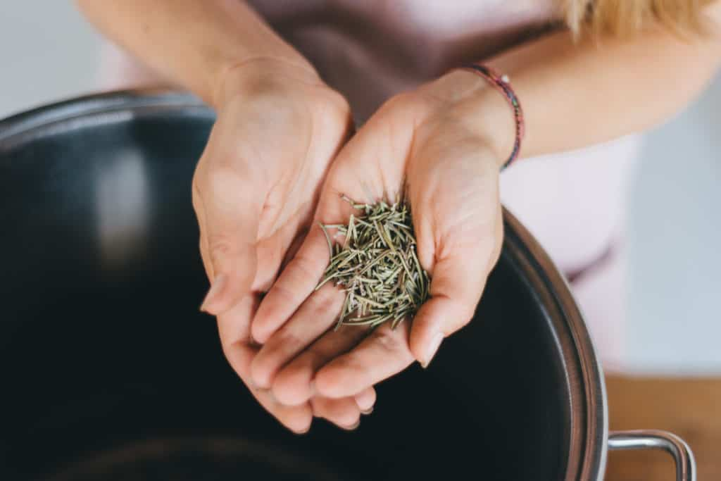 close up of hands hold herbs over a steel pot