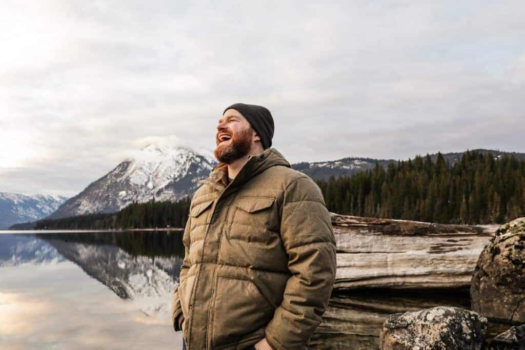 man with mouth open smiling wearing a hat and jacket standing in front of a lake and mountains