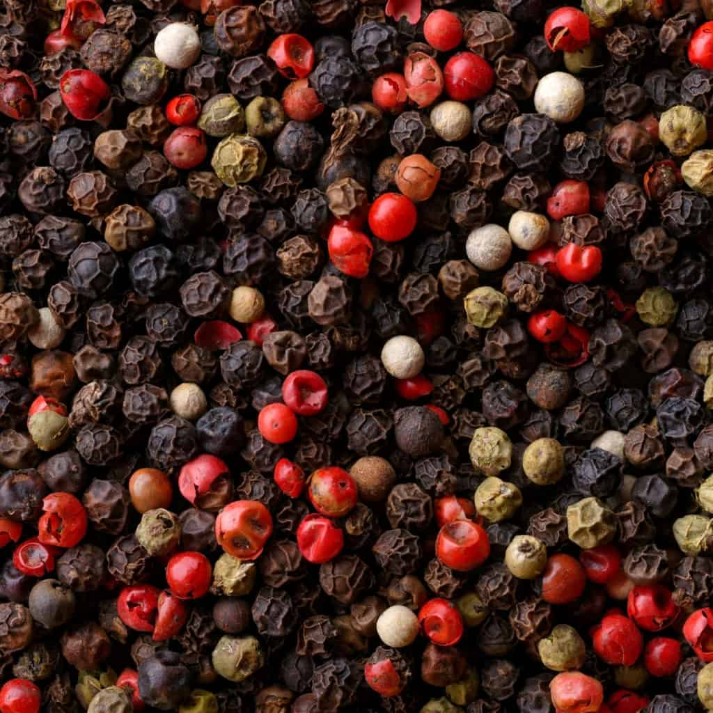 closeup of red, black, green and white peppercorns