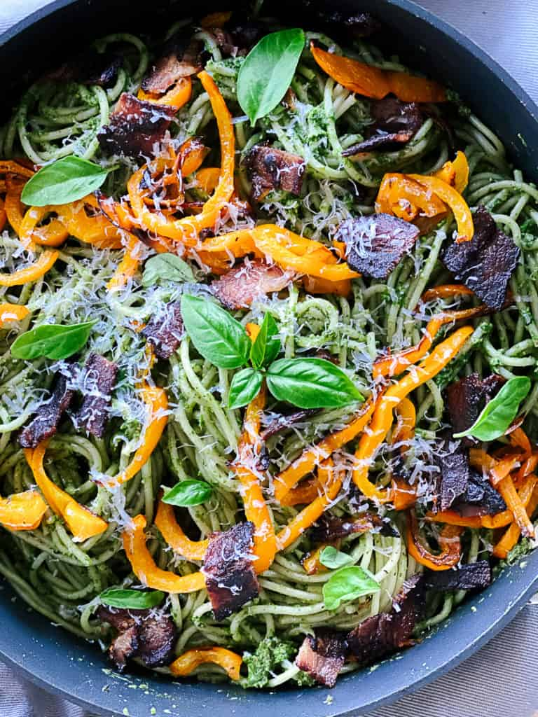 serving pan filled with spinach pesto pasta with bacon