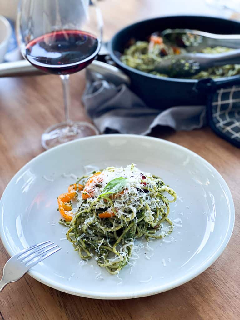 drink with dinner plate with a serving of pesto pasta with bacon