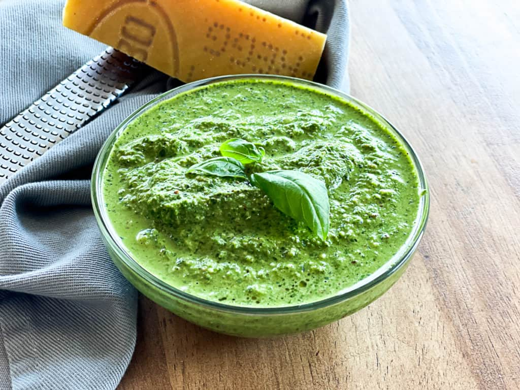 spinach pesto in a bowl next to parmesan cheese