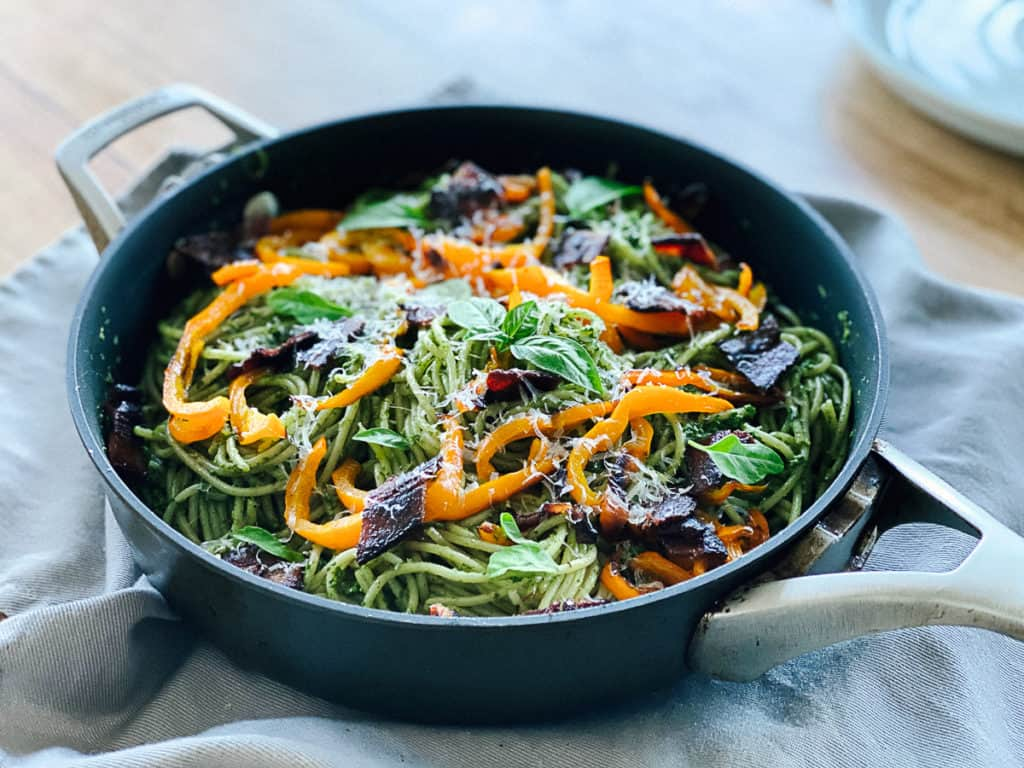 side view of spinach and pesto pasta with vegetables on a table