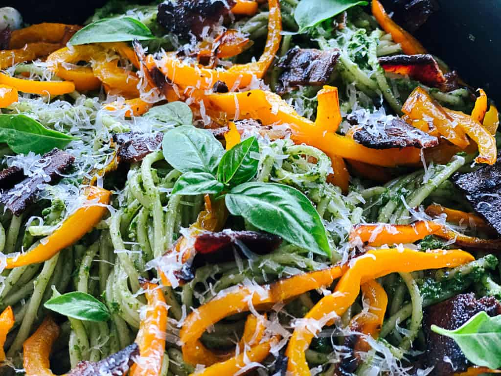 closeup of fresh basil on side view of spinach pesto pasta with veggies