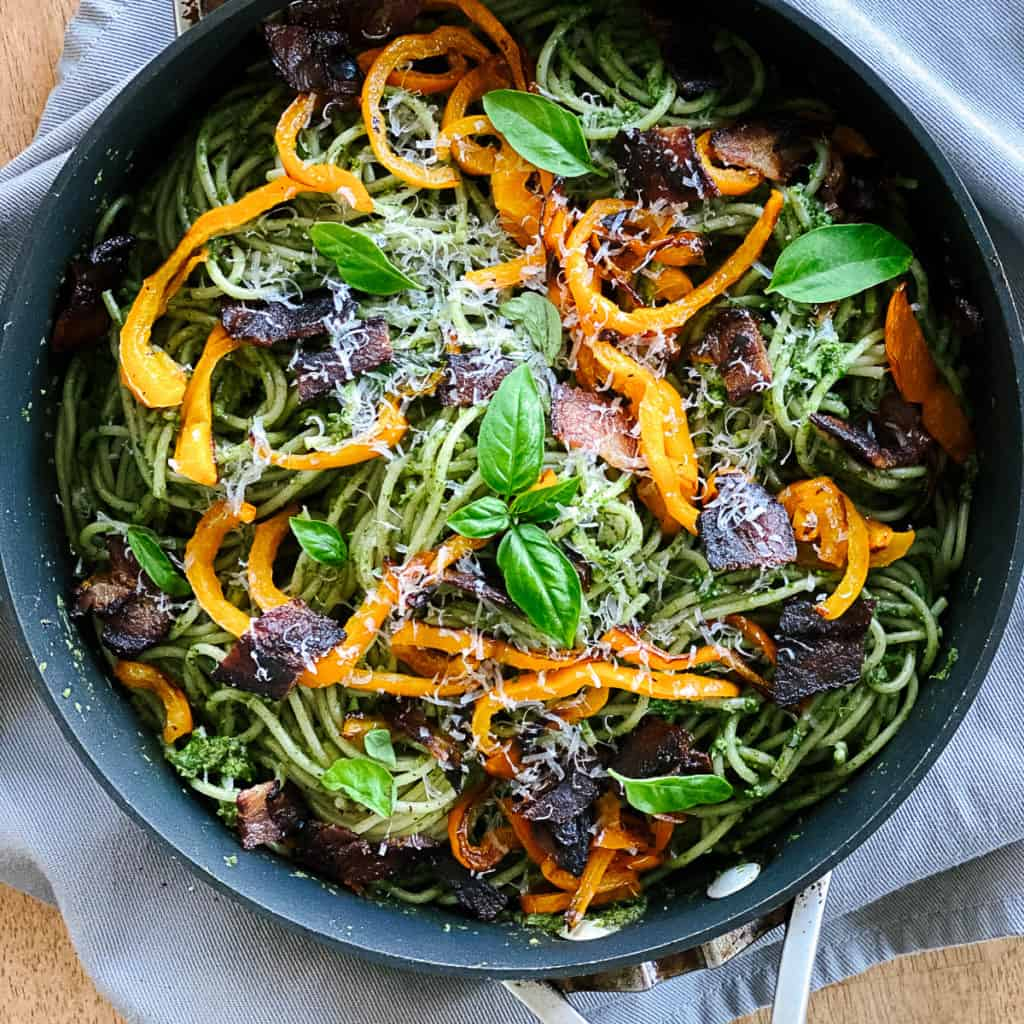 top shot of large pan with spinach pesto pasta with bacon peppers and basil