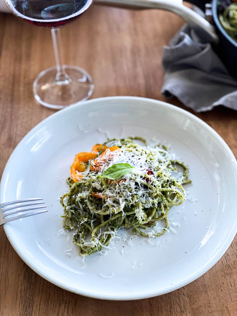 dinner plate with spinach pesto pasta topped with parmesan cheese
