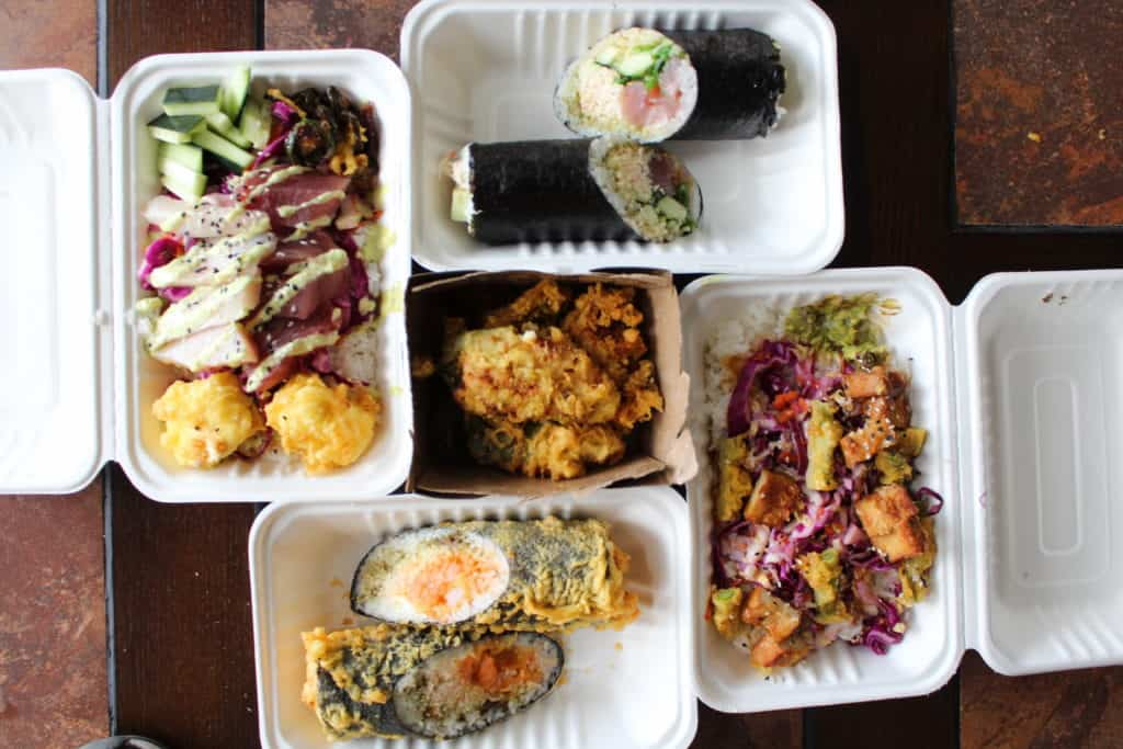 sushi burrito, fried sushi burrito, poke bowl, vegan bowl, and fried appetizer, all in take out containers