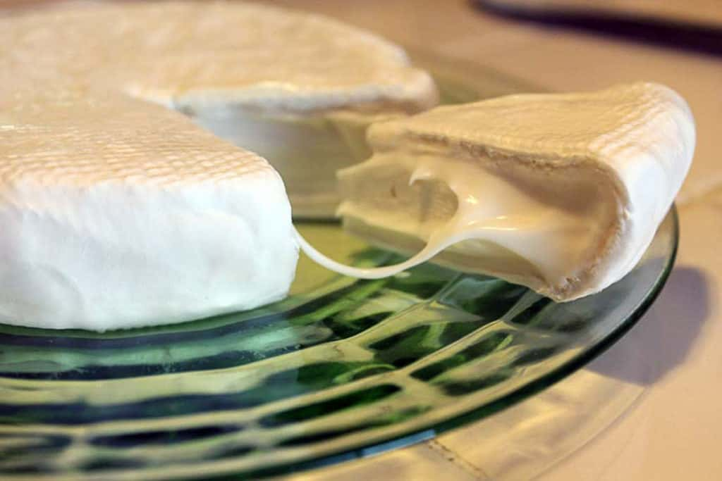 a round of brie cheese with a wedge cut cut and pulled out from the wheel, on green glass plate