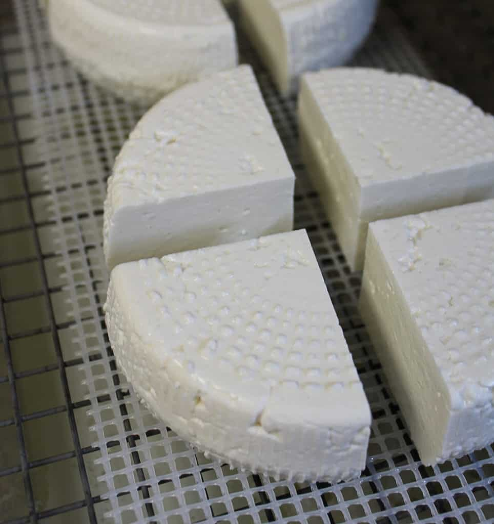 a quartered wheel of feta cheese on a rack