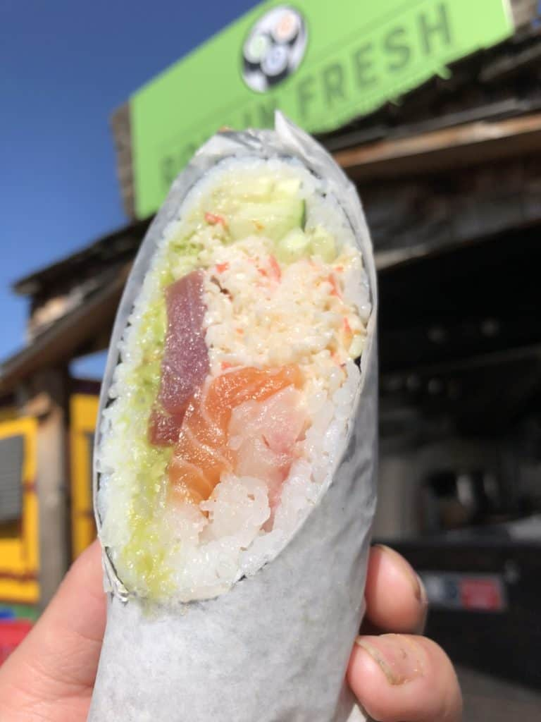 close up of sushi burrito with rollin fresh storefront in the background