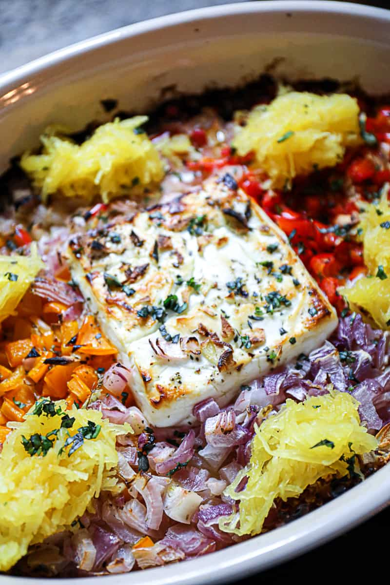 Top shot of baked feta with peppers in casserole dish.