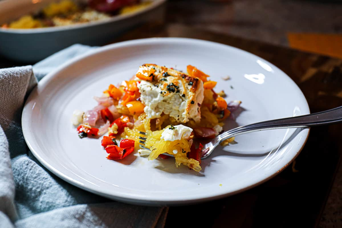 Fork full of baked feta dish with veggies served on a round white plate.
