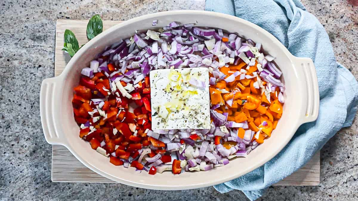 Diced vegetables arranged in a white baking dish with feta in the middle.