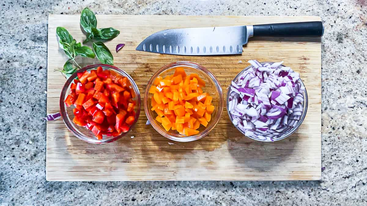 Three small bowls of diced vegetables on wooden cutting board next to knife.