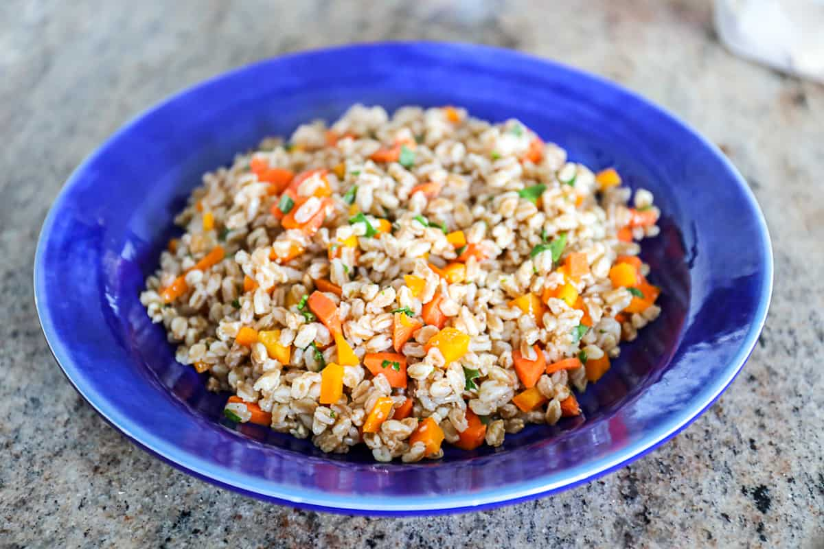 Farro salad with roasted vegetables on blue plate.