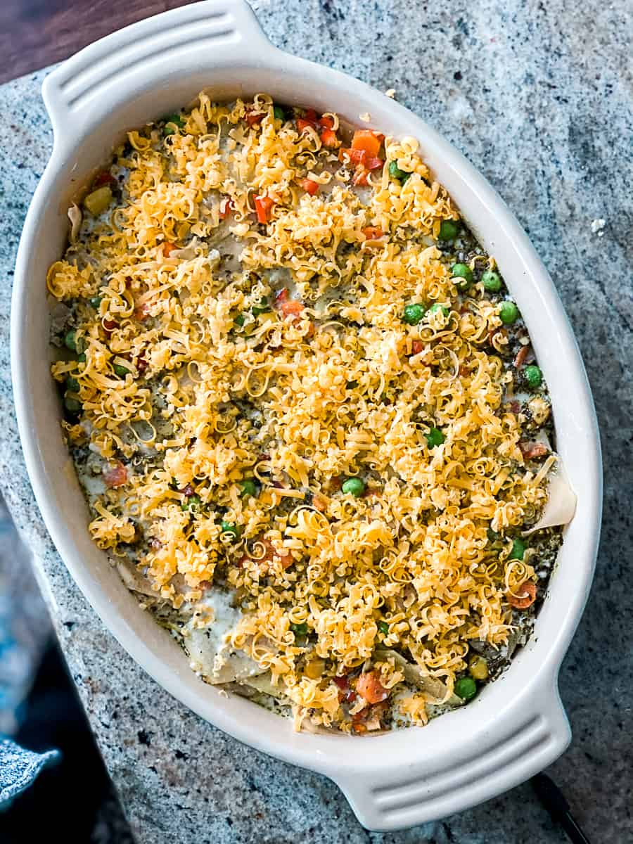 Top shot of frozen mixed vegetables potato au gratin topped with grated cheese in white casserole dish.