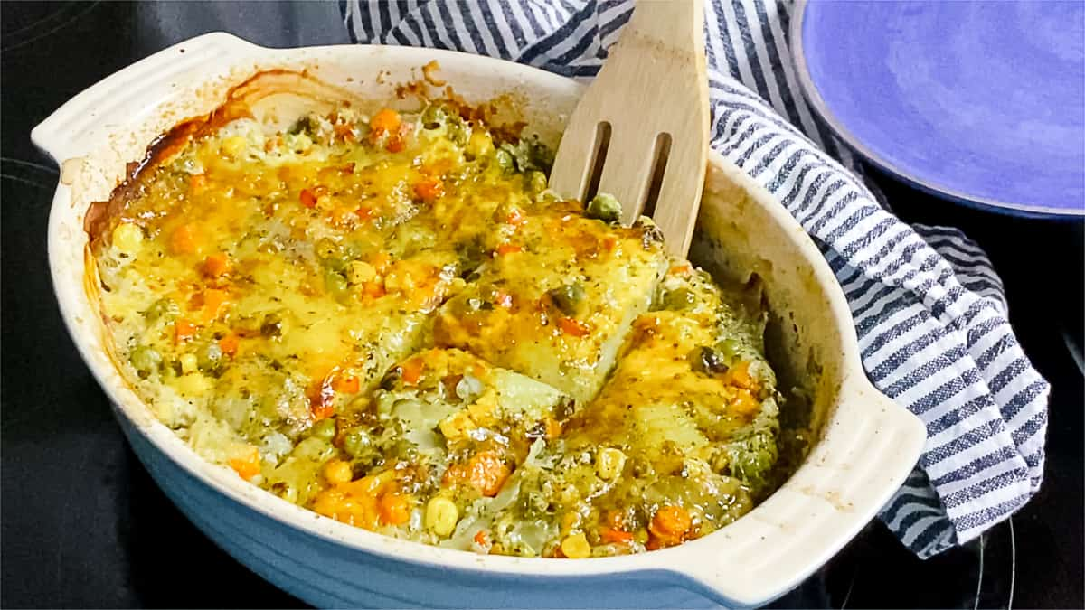 Wooden spoon scooping serving of potato and vegetable casserole topped with grated cheese out of white casserole dish.