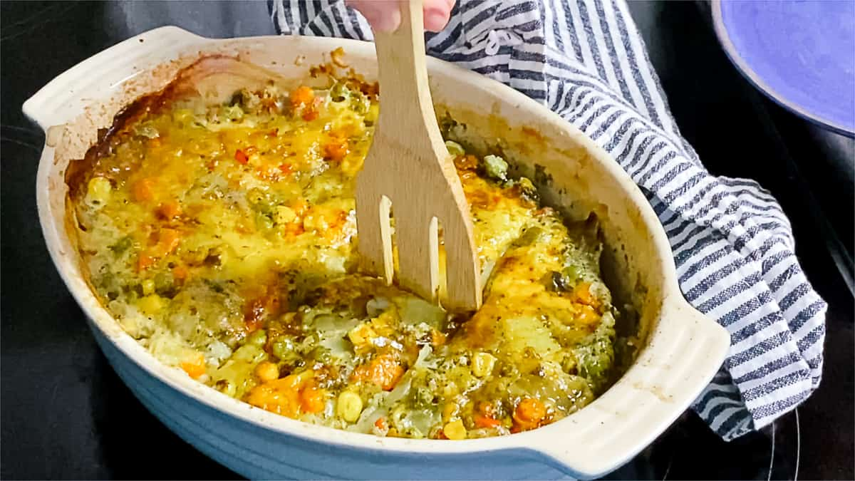 Wooden spoon cutting frozen mixed vegetables potato au gratin topped with grated cheese in white casserole dish.