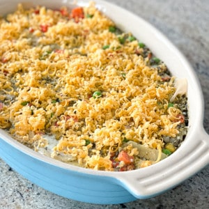 Top shot of potato and vegetable casserole topped with grated cheese in white casserole dish.