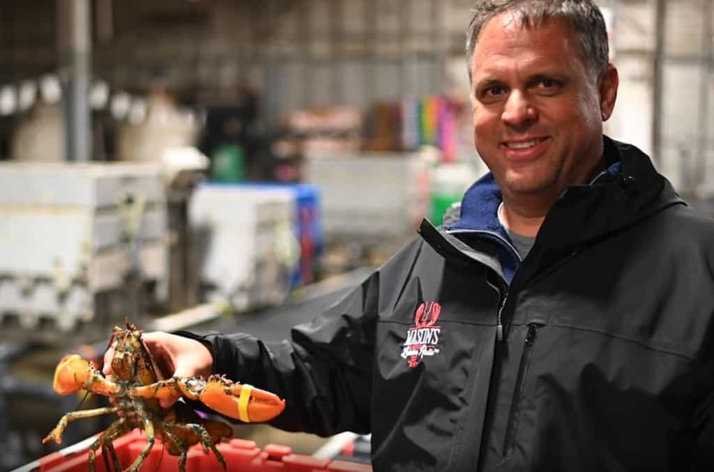 man smiling holding a lobster