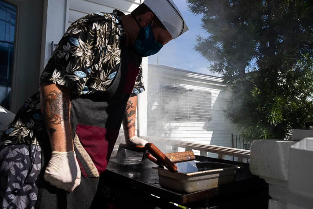 man smashing burger patties on the griddle