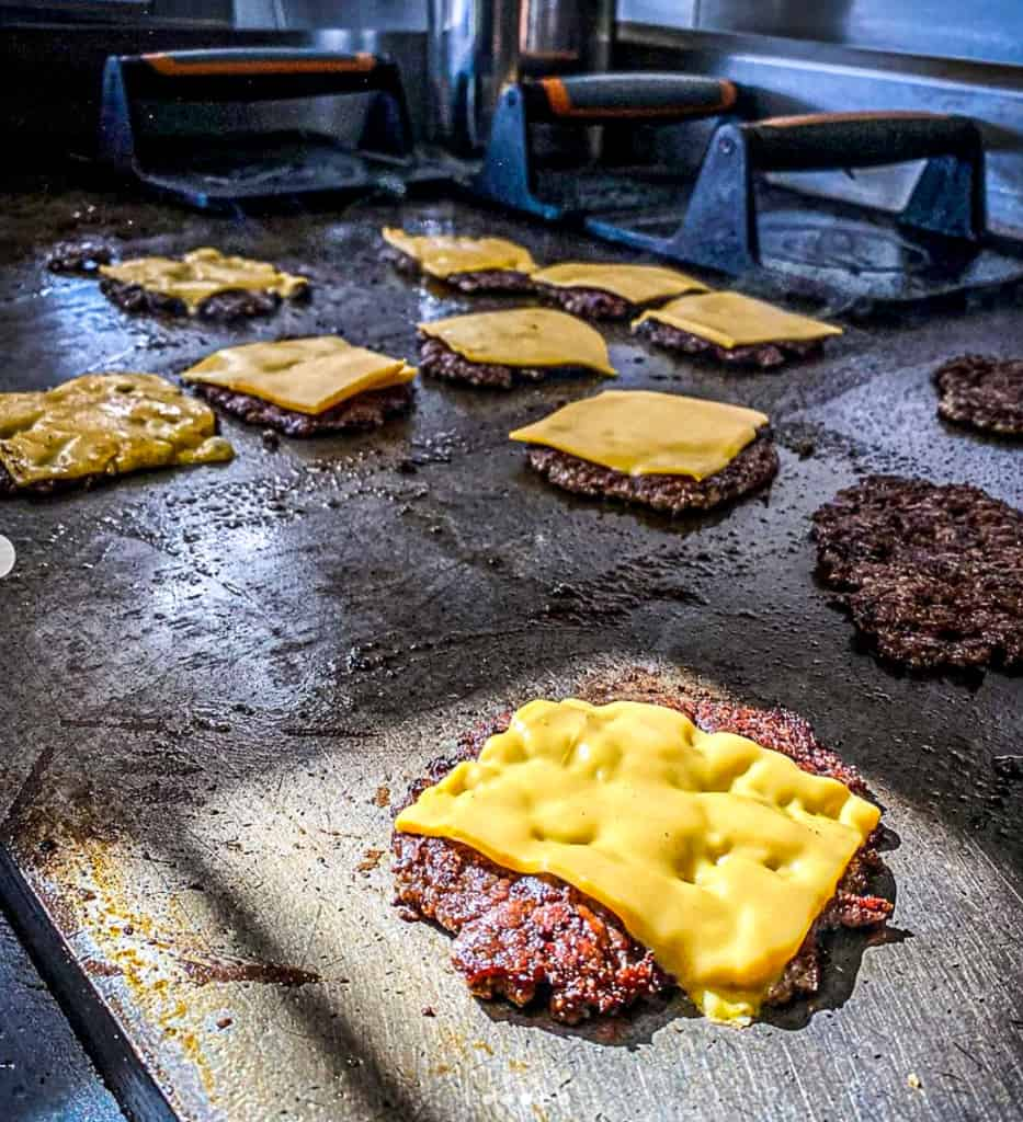 smash burgers on a grill with cheese melting on top