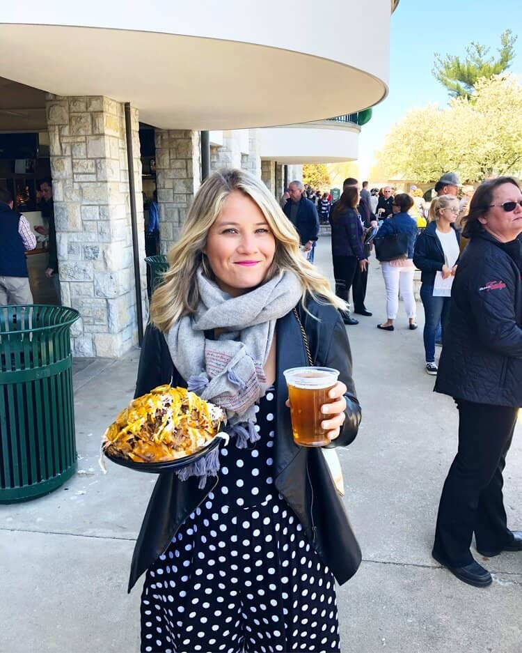 woman in a scarf smiling, holding nachos and a beer
