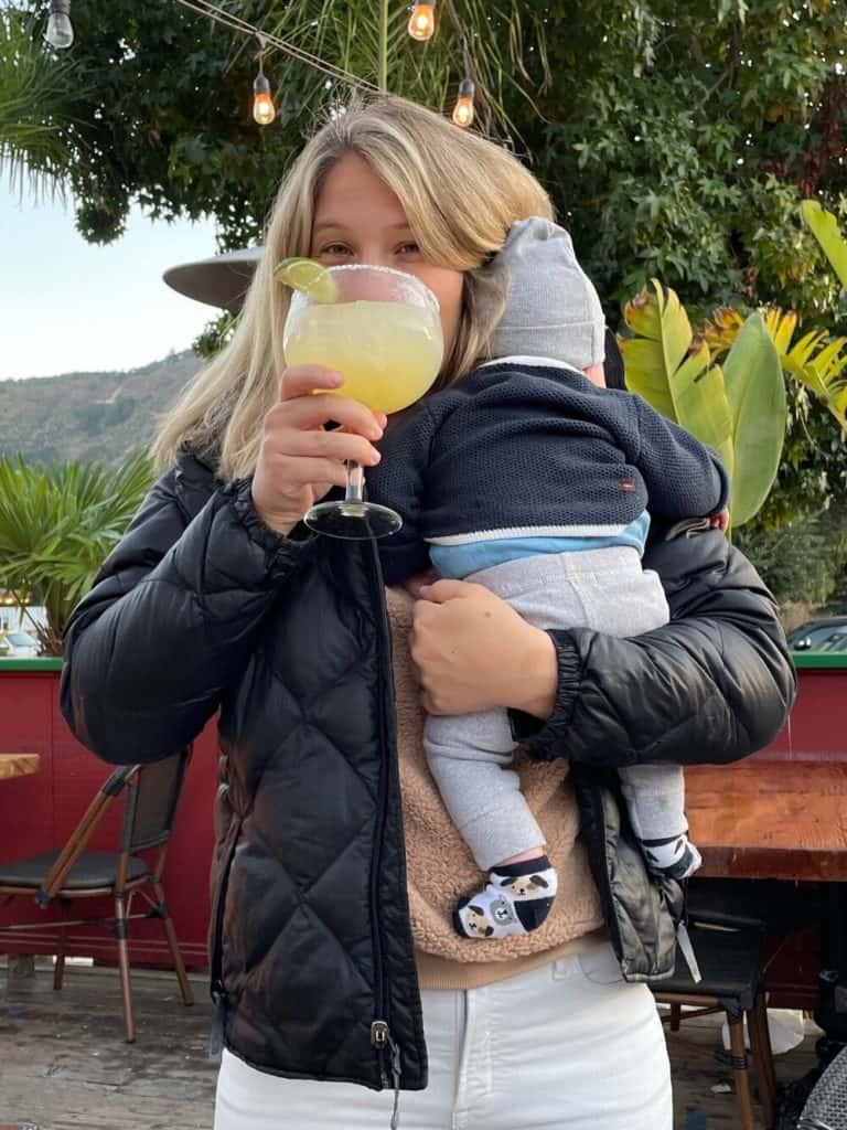 woman holding baby while drinking a margarita
