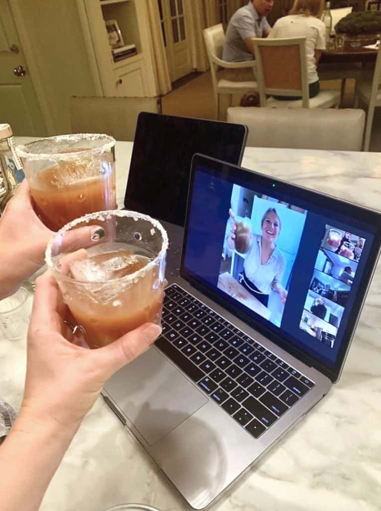 two people holding drinks toward a computer screen with a zoom happy hour on the laptop