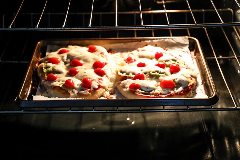 Two ravioli pizzas on flatbread cooking in oven.