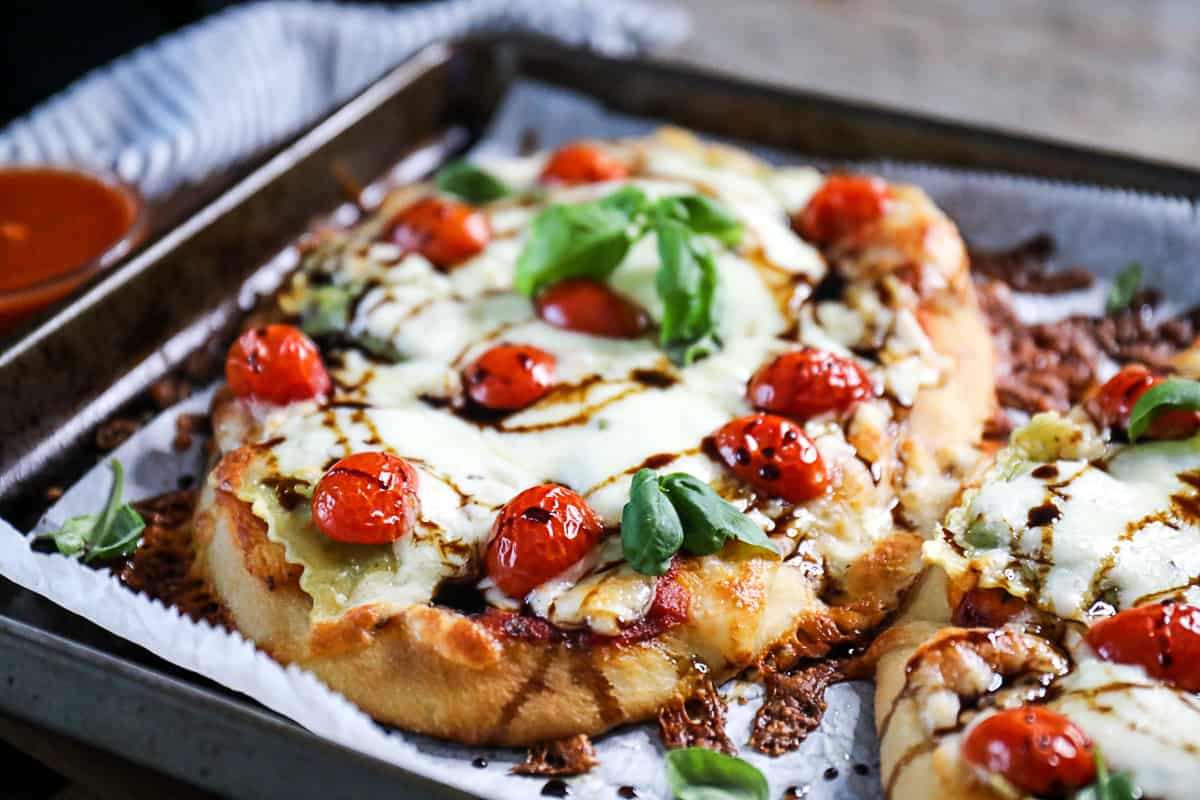 Top shot ravioli pizza on flatbread, topped with mozzarella cheese and cherry tomatoes.