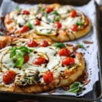 Top shot of small pizza made on naan and topped with mozzarella cheese and tomatoes.