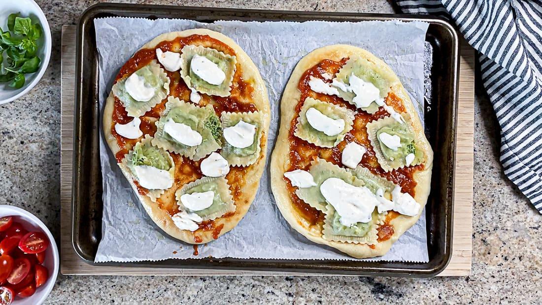 Two flatbread pizzas with ravioli, tomato sauce, and alfredo sauce, on baking sheet.
