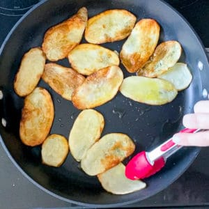 Tongs moving thinly sliced potatoes around on skillet.