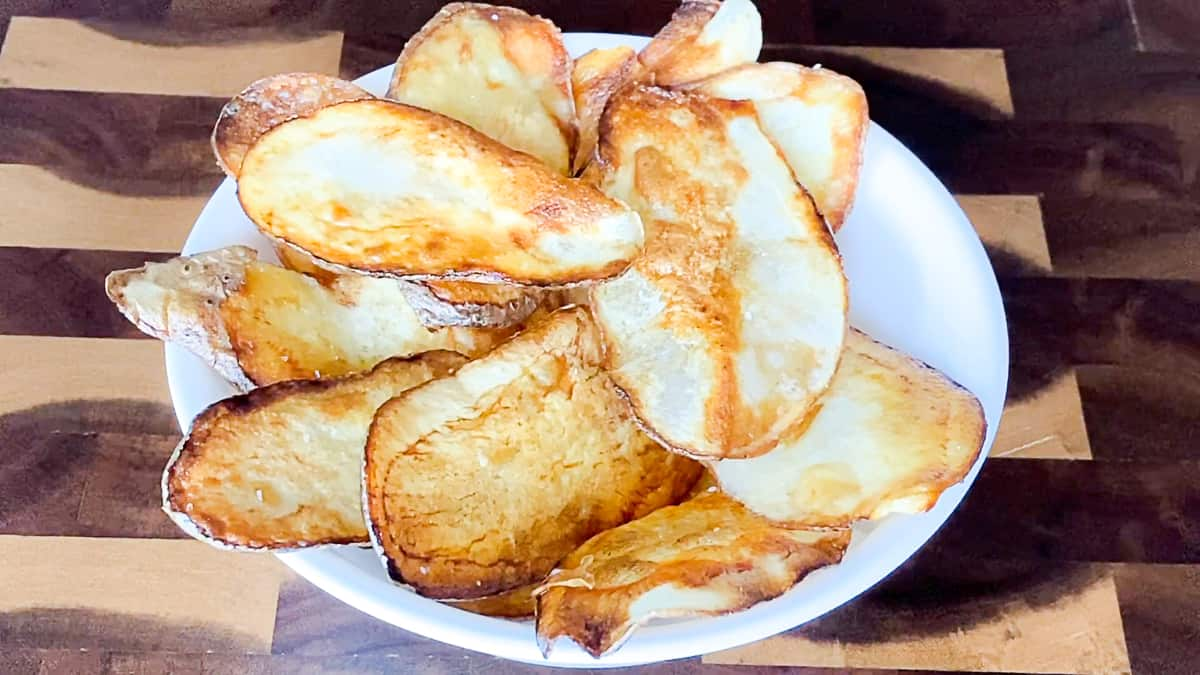 Pan fried potato chips on white plate on countertop.