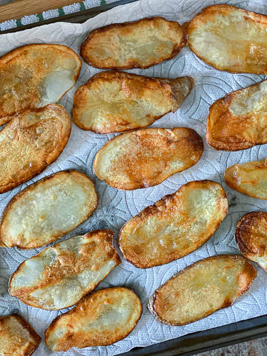 Pan fried potato chips arranged in rows on paper towel on baking sheet.