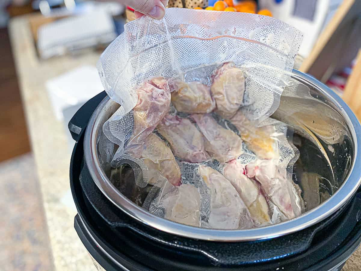 Uncooked chicken wings in sealed plastic bag being placed in sous vide bath.