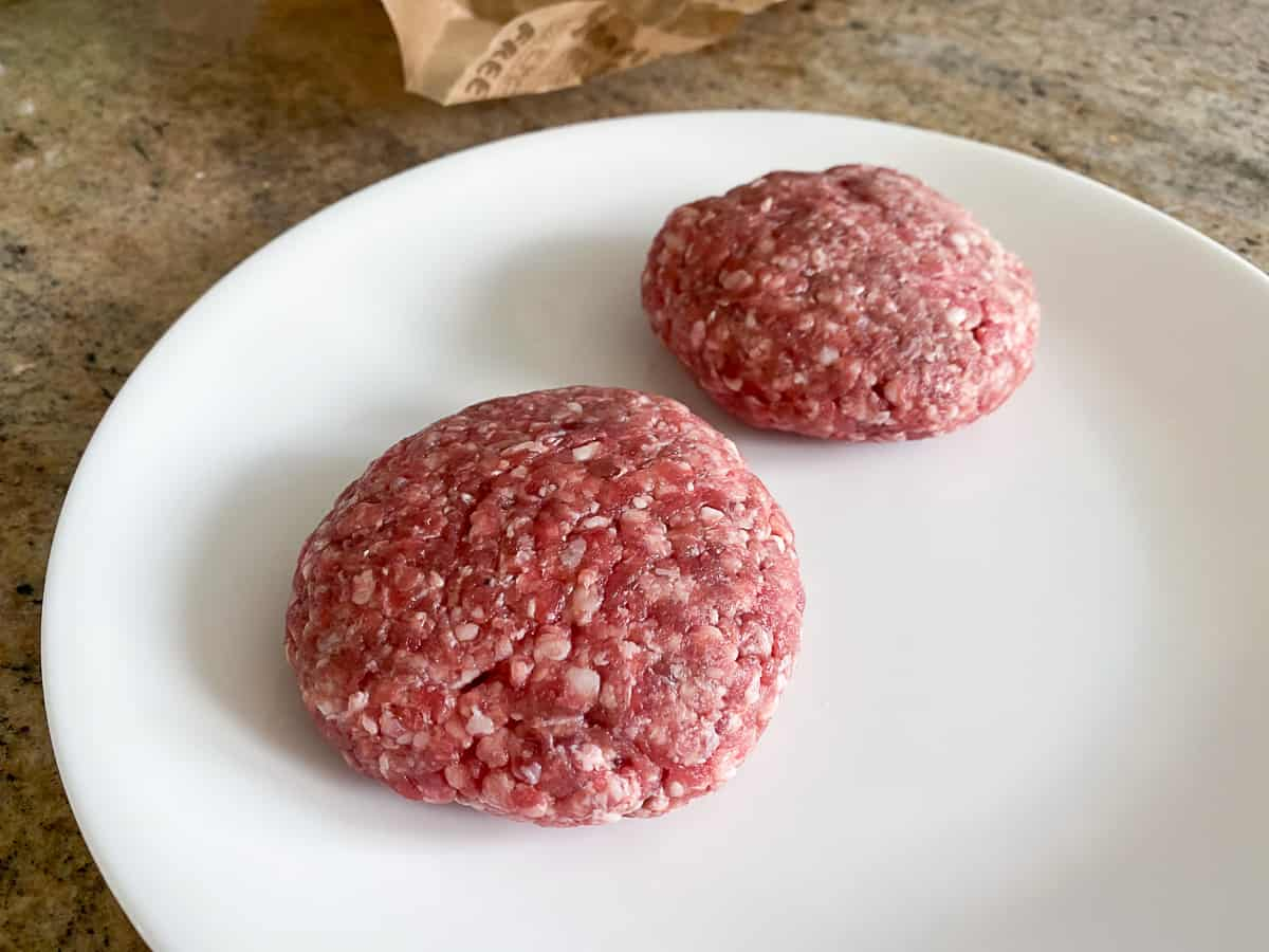 Two uncooked hamburger patties on white plate.