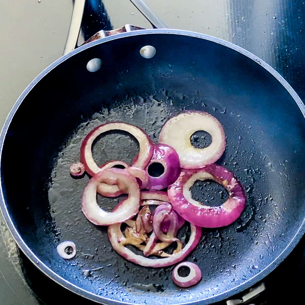 Onions cooking in black skillet.